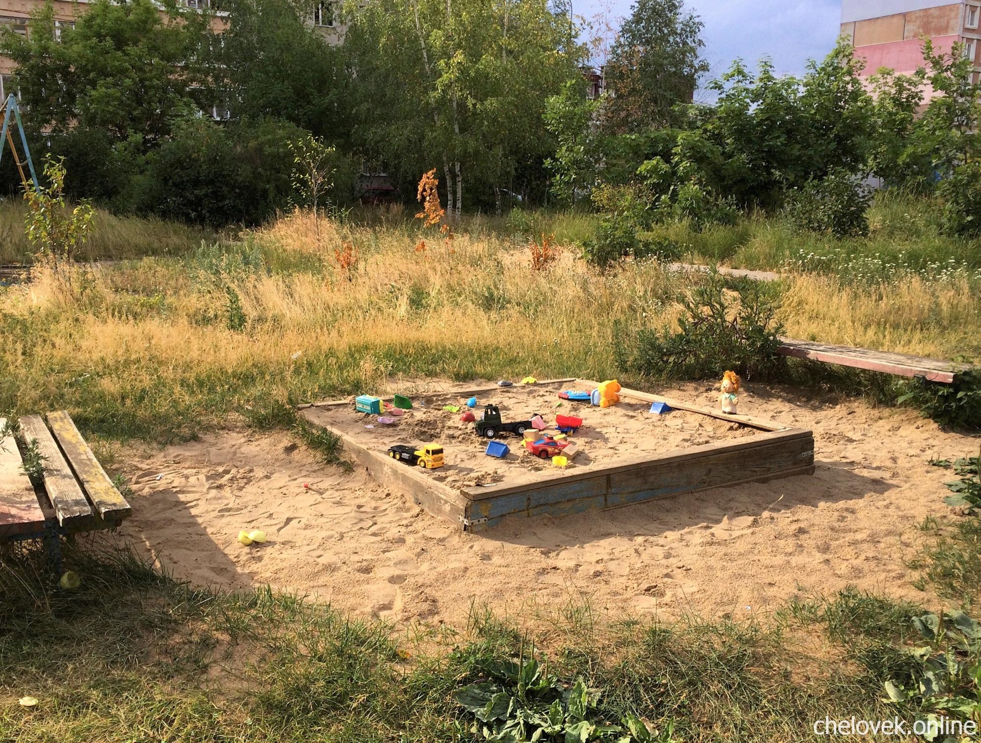 Детская песочница с игрушками во дворе