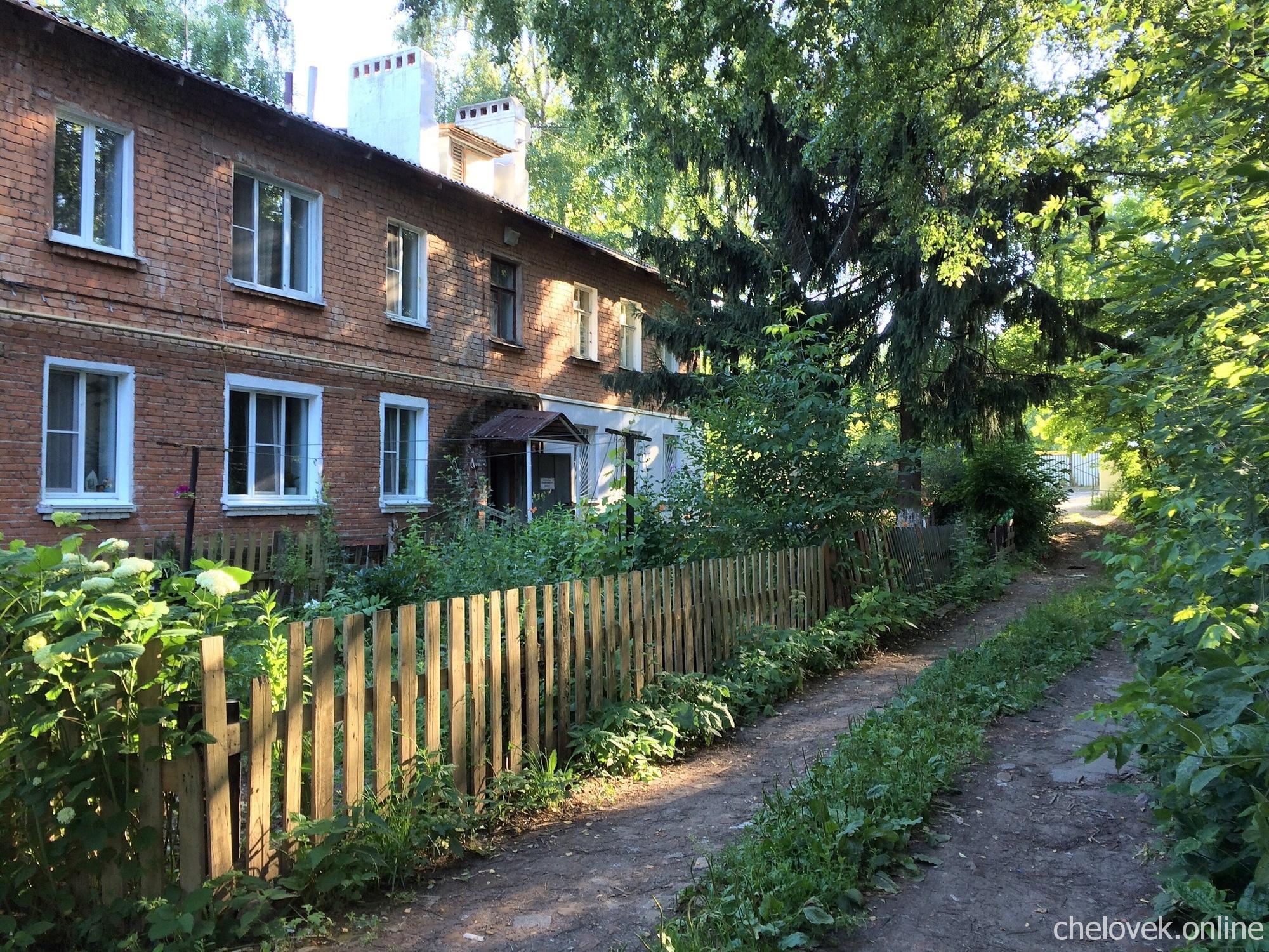 Старый кирпичный дом, забор, дорога. Нижний Новгород